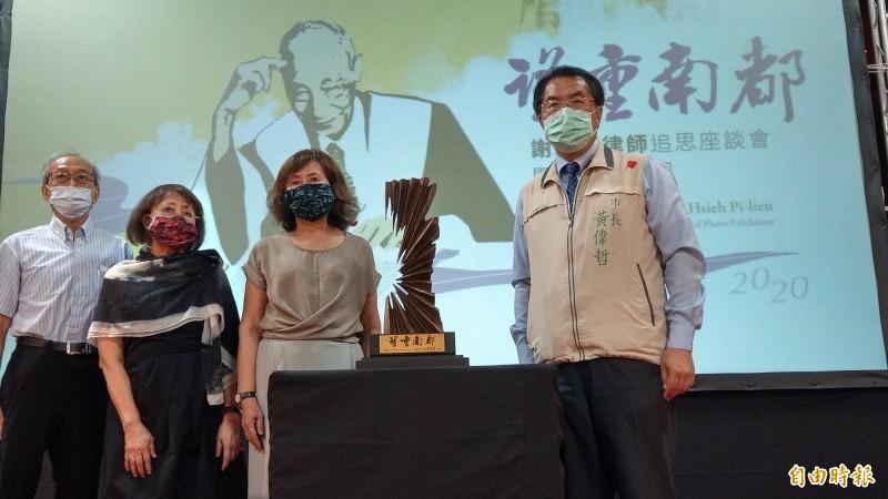 台南市長黃偉哲(右)致贈雕刻作品給已故資深律師謝碧連的家屬,感念謝碧連對文史及藝壇的貢獻。(記者劉婉君攝)