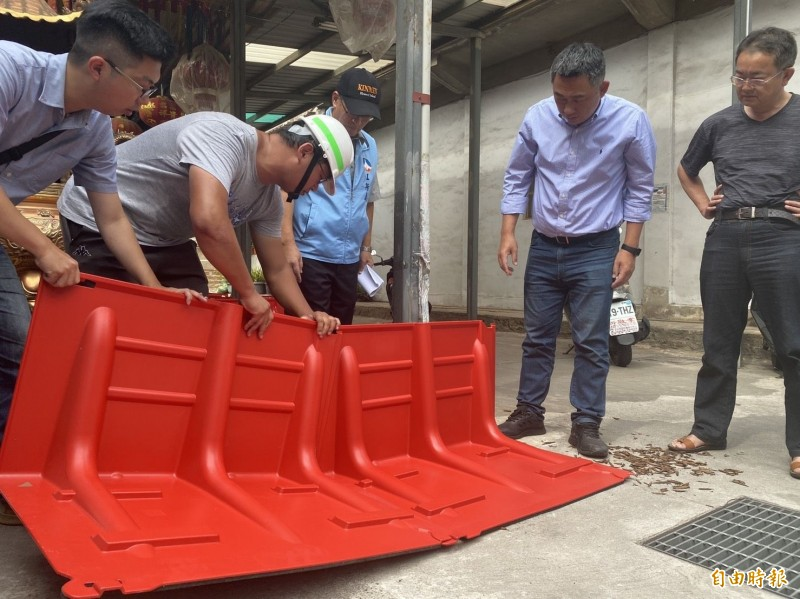 金門縣金城鎮公所人員進行防洪板的銜接設置作業。(記者吳正庭攝)