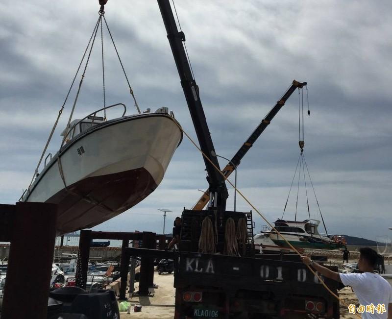 金門縣港務處協助民間將碼頭船隻吊起安置岸上。(圖由金門縣政府提供)