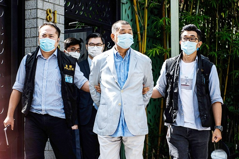 Hong Kong police officers escort tycoon Jimmy Lai, center, from his Kowloon home after he was arrested under the new National Security Law yesterday morning.  Photo: AFP