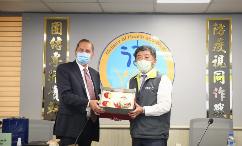 美國衛生部長阿札爾(左)參訪中央流行疫情指揮中心,並與指揮官陳時中(右)交換紀念品。(中央流行疫情指揮中心提供)
