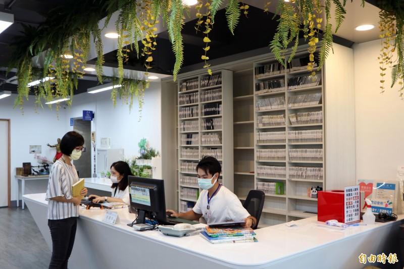 新北市立圖書館三重五常分館服務櫃檯垂墜著藤蔓,營造舒適的自然氛圍。(記者陳心瑜攝)