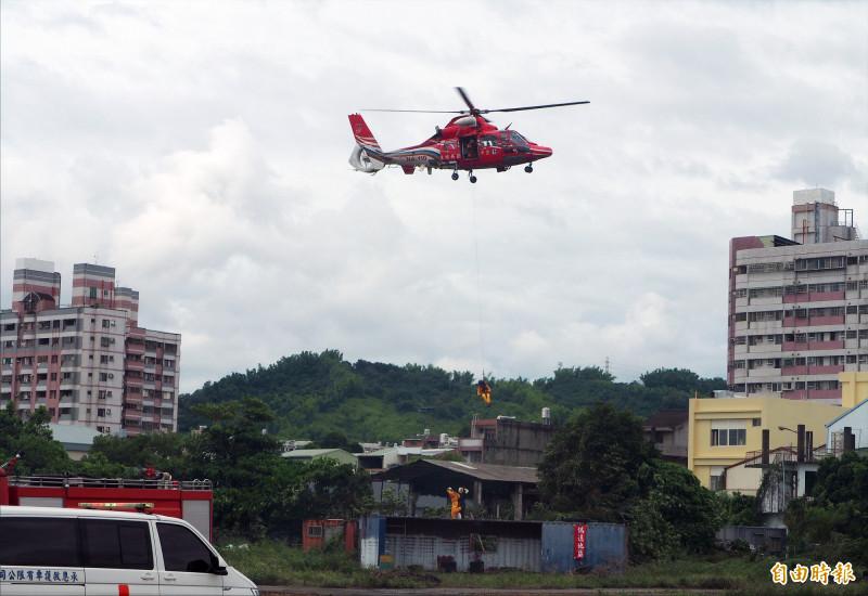 空勤直升機載搜救人員垂降救援受傷民眾,再吊掛上機送醫。(記者陳鳳麗攝)
