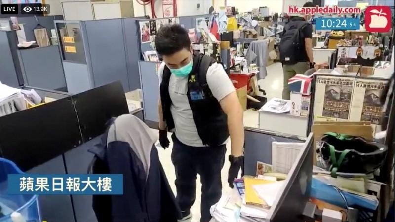 香港警方昨日大動作突襲香港壹傳媒總部,還被拍攝到翻閱記者辦公桌上的資料。(路透)