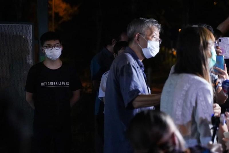 前香港眾志秘書長黃之鋒11日晚間也到大埔警署聲援周庭,當周庭在鎂光燈下受訪時,他在背後默默守望,這畫面讓不少網友感動直呼「超暖」。(圖擷取自臉書_黃之鋒 Joshua Wong)