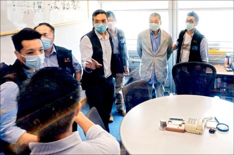 港警昨大搜捕《壹傳媒》,創辦人黎智英(右二)被扣上手銬,押到蘋果日報大樓內協助查證。(中央社)