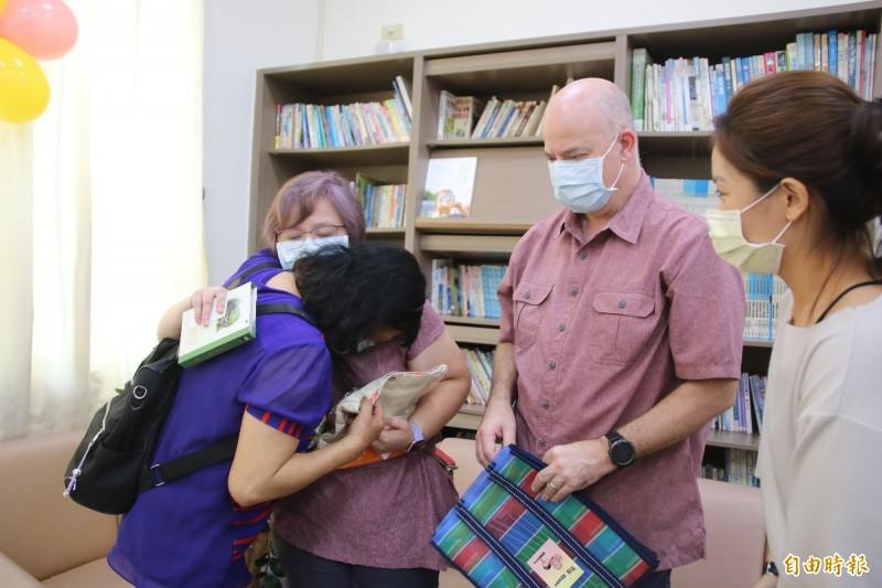 扶養俊俊2年的寄養媽媽陳瑞滋(左)離情依依,與收養俊俊的路易斯夫婦相擁而泣。(記者鄭名翔攝)