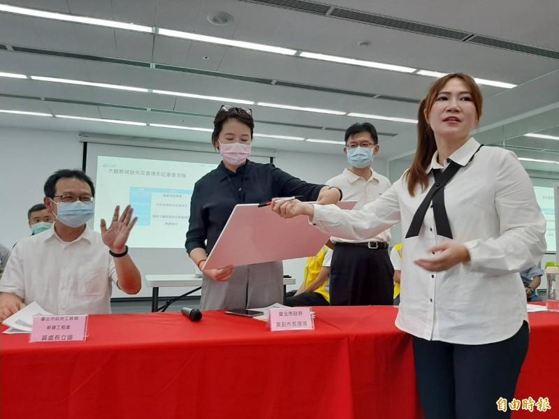 市議員陳怡君(右)當眾拿出一份不漏水保證書,副市長黃珊珊(左二)不願簽字。(記者郭安家攝)