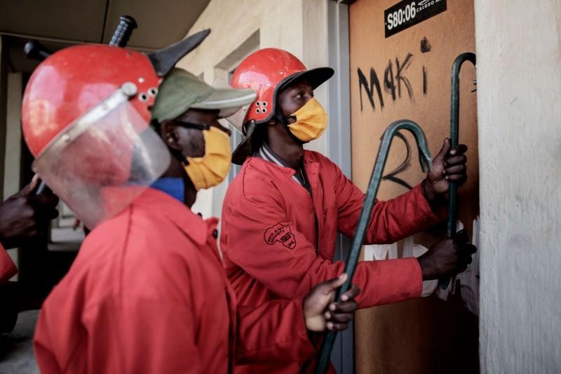 南非紅螞蟻(The Red Ants)成員使用撬棍打開一扇門。(法新社)