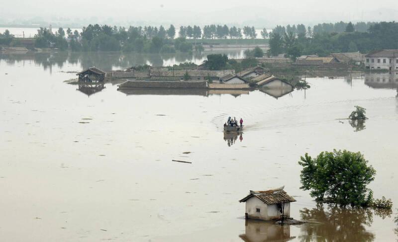 北韓異常大量降雨,造成嚴重洪災,上百棟平房被洪水淹過或摧毀,農業區也有大面積的稻田被淹沒。圖為北韓2012年7月底颱風淹水畫面。(法新社資料照)