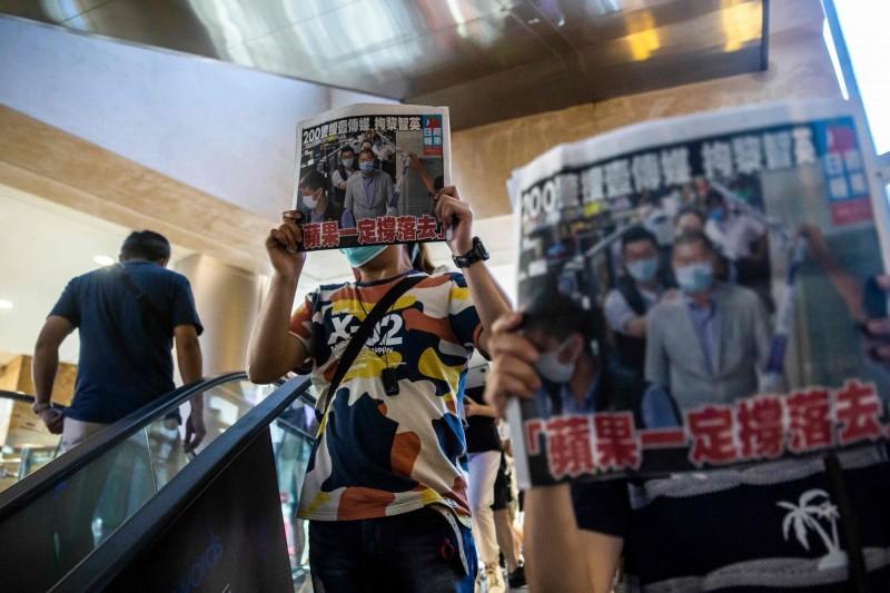香港網友在昨日晚間發起「和你Sing」示威行動,舉起當天的《蘋果日報》抗議。(美聯社)
