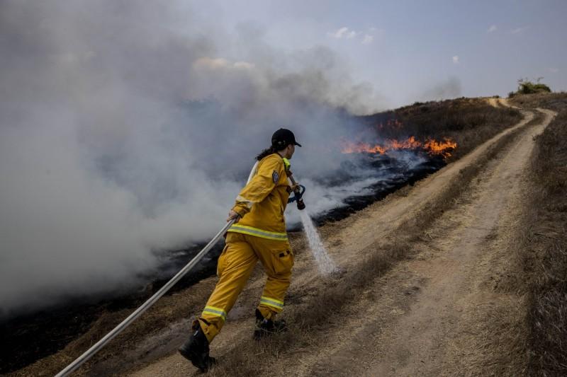 1名以色列消防員試圖撲滅巴勒斯坦發射的燃燒氣球所引致的大火。(美聯社)