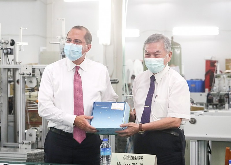 Vice Premier Shen Jong-chin, right, presents US Secretary of Health and Human Services Alex Azar with a box of masks while visiting the Chang Hong Machinery Co factory in New Taipei City's Wugu District yesterday.  Photo: CNA