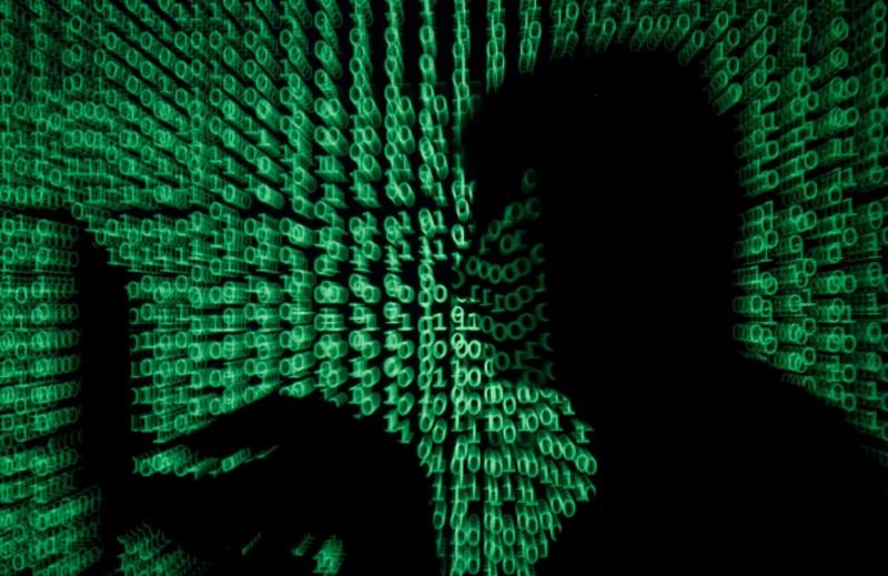 電腦使用者與螢幕上投射的電腦程式碼。(路透檔案照)