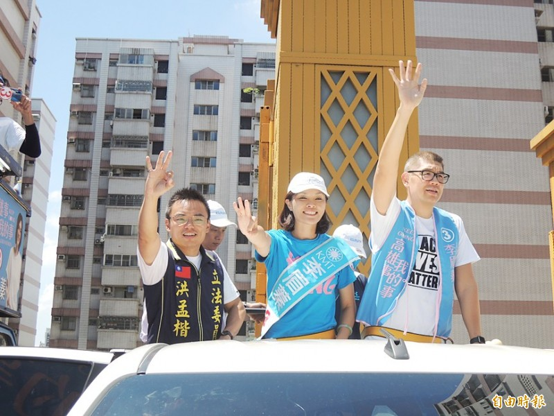 Kaohsiung City Councilor Jane Lee, center, the Chinese Nationalist Party's (KMT) Kaohsiung mayoral by-election candidate, waves alongside KMT Legislator Hung Meng-kai, left, and National Policy Foundation Vice Chairman Sean Lien, at a rally in the city yesterday. Photo: Wang Jung-hsiang, Taipei Times