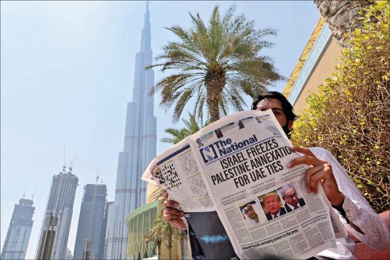 一名男子十四日在阿聯的杜拜街頭閱讀當地一份英文報,該報頭版以斗大字樣報導以阿關係正常化。(法新社)