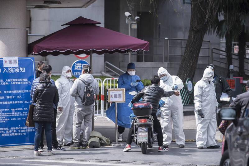 圖為上海一間醫院的醫護人員在外院對入院者進行體溫測量情況。(彭博)