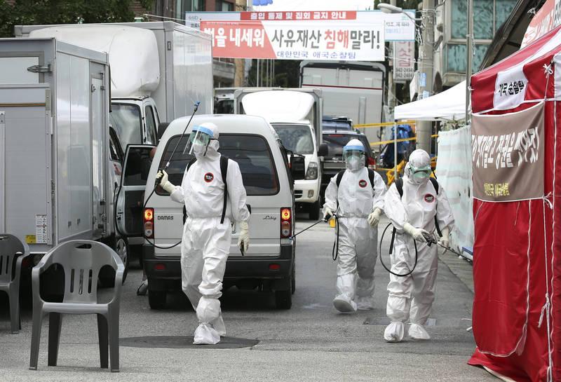 南韓正爆發第3波武漢肺炎疫情,防疫人員將患者曾到過的街道消毒。(美聯社)