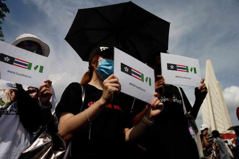 泰國曼谷示威者在6日的集會上,要求泰國政府起草新憲法舉辦選舉,並舉著有台灣旗、黑底洋紫荊旗的「奶茶聯盟」手牌,象徵亞洲各國以民主精神結盟合作。(路透)
