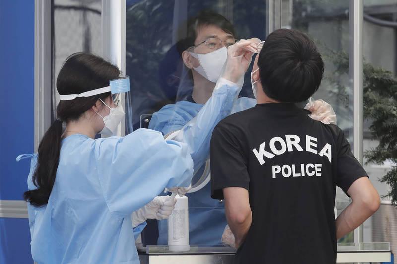 南韓「愛第一教會」疫情延燒,首爾有警察被信徒傳染,防疫人員採檢其他警察的檢體。(美聯社)