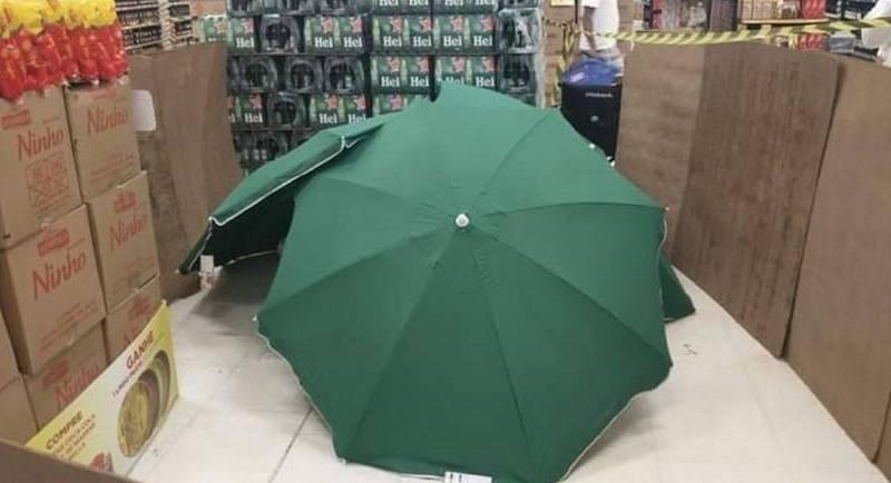 銷售員猝死店內,賣場以雨傘遮蔽屍體,並以紙箱等物品隔開走道。(圖擷自推特)