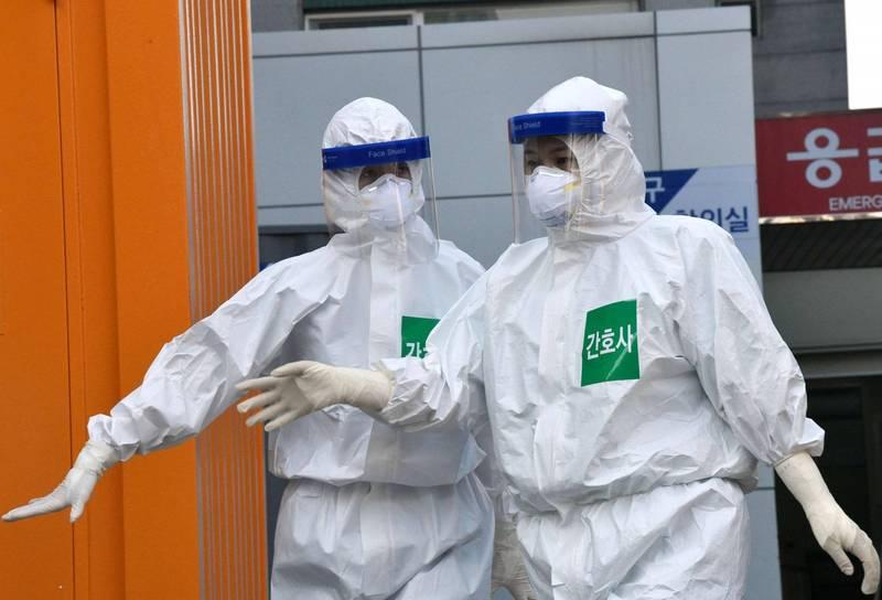 南韓京畿道坡州市一間星巴克,傳出和55名患者感染武漢肺炎(新型冠狀病毒病,COVID-19)有關。南韓防疫人員示意圖。(法新社)
