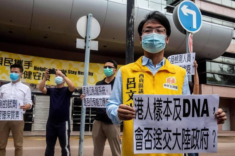 香港9月1日將進行先前宣布的「自願性普及社區檢測」,不少民眾、政治人物提出質疑,擔心檢測樣本被「送中」。圖為香港民主派議員呂文光針對疑慮進行抗議。(法新社)