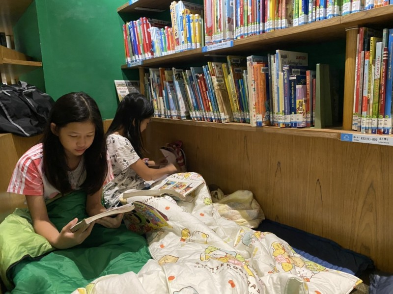 學童夜宿在高市圖國際繪本中心,抱著繪本夜讀捨不得入睡。(記者許麗娟翻攝)