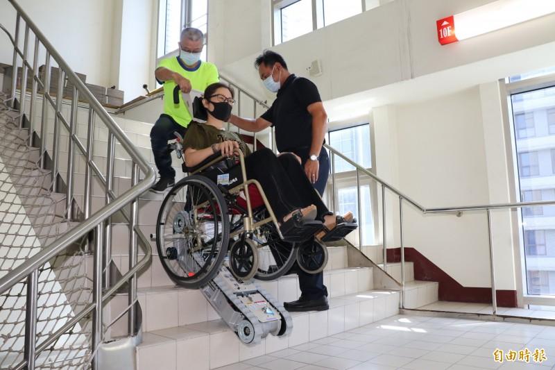曾茂燦和太太魏桂芬(坐者)操作體驗輪椅型履帶爬梯機上下樓梯。(記者何玉華攝)