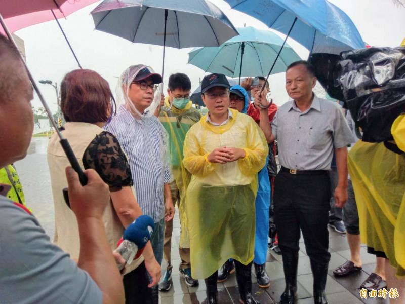 高雄市長陳其邁(左3)聽取水利局長蔡長展(中)、消防局長李清秀(右1)報告排水狀況。(記者黃旭磊攝)