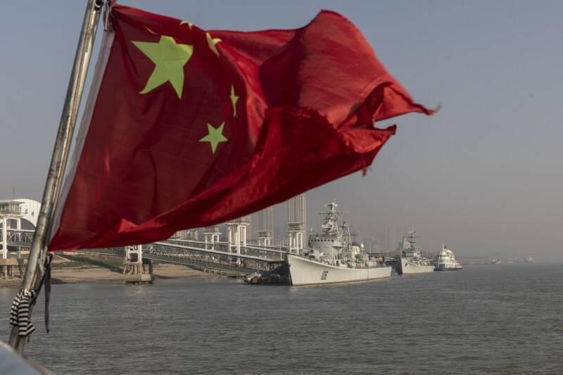 越南政府今天指控,中國在南海爭議海域進行軍事演習侵犯了越南主權,還說北京此舉讓建立「南海行為準則」的談判複雜化。圖為中國國旗與解放軍軍艦。(彭博資料照)