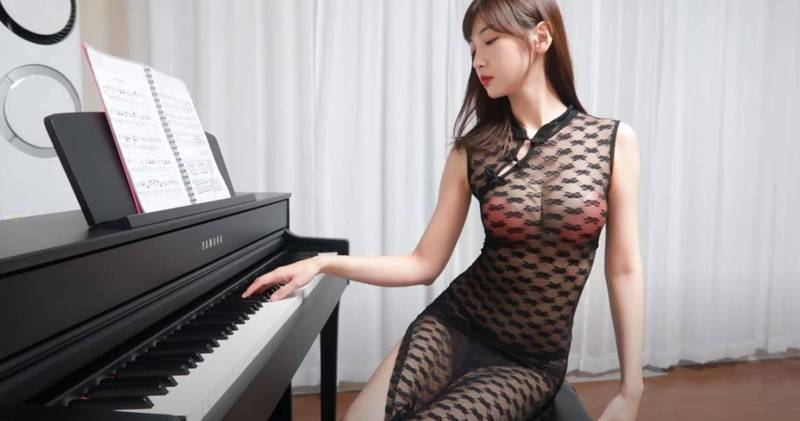 韓國YouTuber「이지Leezy」穿著爆乳透視裝,坐在鋼琴旁邊擺POSE。(圖擷取自YT)