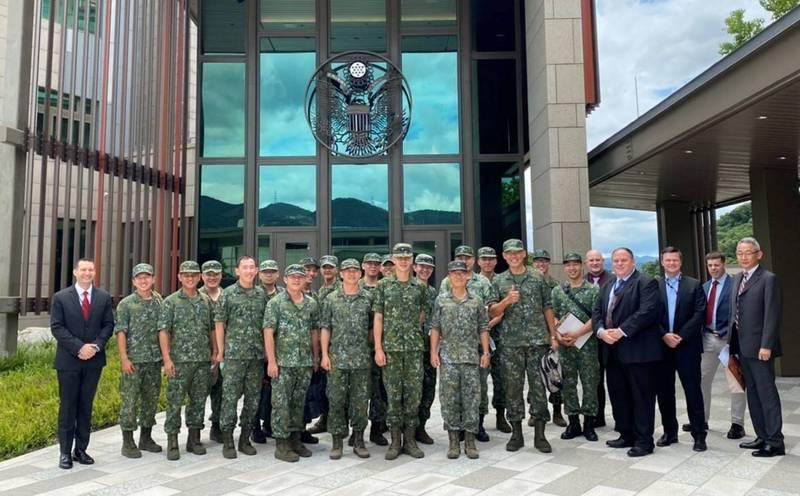 我國陸軍航空601旅官兵著軍服到AIT新大樓內,與美軍部隊進行視訊對話。圖為601旅官兵與美方官員在AIT新大樓前的合影。(圖:擷取自美國在台協會AIT臉書專頁)