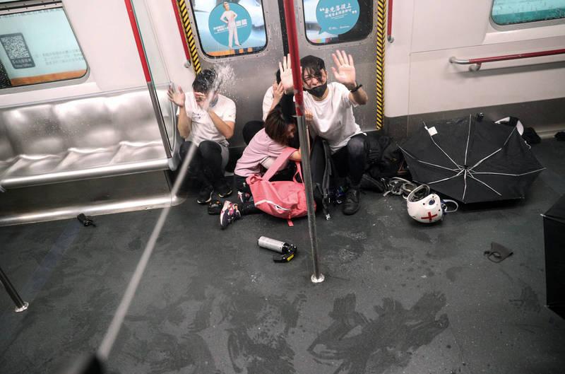去年8月31日,港警在驅散反送中運動示威者時,衝入港鐵車廂內,無差別朝市民以胡椒噴霧掃射,即使市民無助求饒仍不罷手,並持續以胡椒噴霧近距離噴射市民頭部。該畫面成為多家媒體的頭板,更被視為去年反送中運動中「831太子站襲擊事件」的代表性畫面。(美聯社)