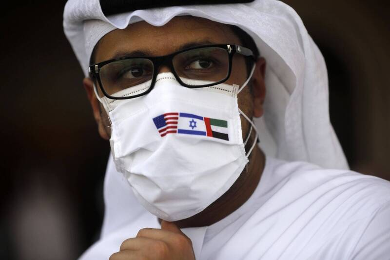 以色列和美國代表搭專機飛抵阿拉伯聯合大公國阿布達比機場,這名阿聯當地男士戴的口罩上還印有阿聯、以色列和美國3國國旗。(歐新社)