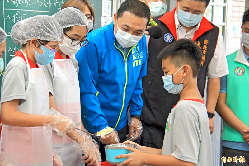 侯友宜視察營養午餐菜色,幫小學生盛飯菜並閒話家常。(記者邱書昱攝)
