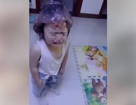 網友貼出影片,可見孩子頭上黏滿史萊姆,面對這種情形,女童感到相當害怕。(圖取自爆廢公社)