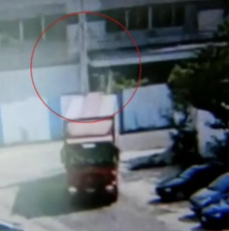 圖中紅色大貨車倒車時,不慎撞倒一旁路燈。(記者許國楨翻攝)