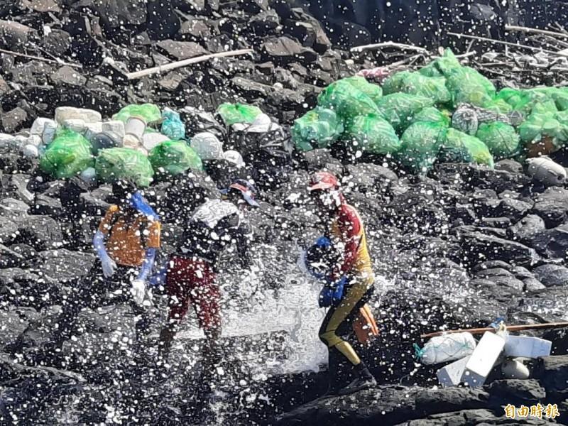 特戰志工清理海廢,不時還被激浪襲擊,搞不清楚流汗還是海水。(記者劉禹慶攝)