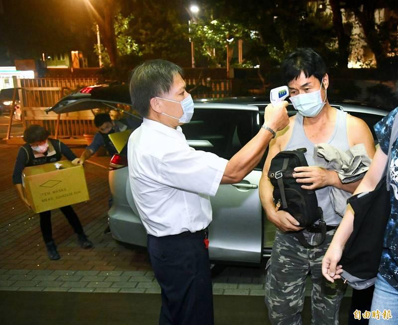 檢調偵辦加利科技公司將中國口罩混入實名制口罩案,晚間將負責人林明進(右)帶回。(記者方賓照攝)