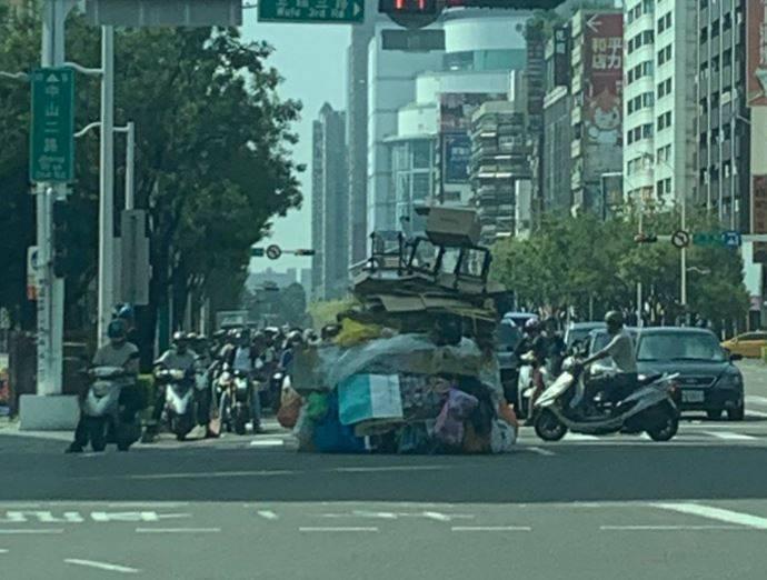 有高雄民眾近日在新崛江周邊馬路目擊一名「熱褲哥」,推著一坨約3公尺、比他還高的資源回收物趴趴走,傻眼直呼「霍爾城堡的移動」。(圖擷取自臉書「爆廢公社」)