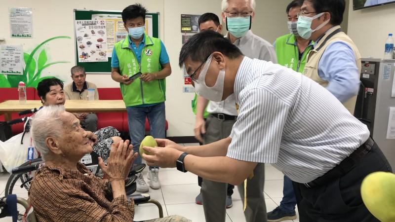 內政部長徐國勇(右)赴南市永春護理之家訪視長者,並贈送每位長輩柚子。(民進黨南市黨部提供)
