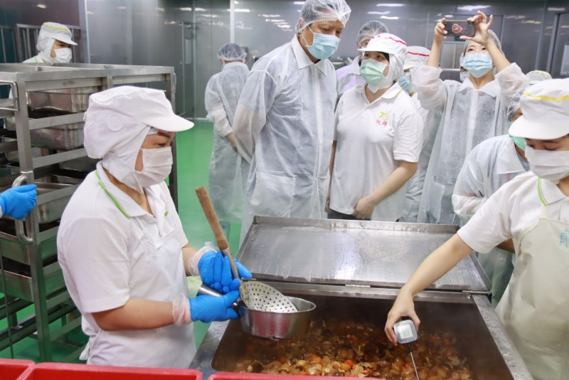 新北市政府副秘書長朱惕之率隊稽查團膳工廠,作業人員以藍芽溫度計量測菜餚溫度。(新北衛生局提供)