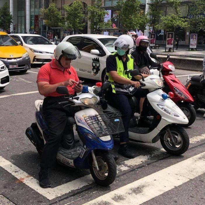 有位男子在等紅燈時專心滑手機,卻沒注意到身旁的警察。(圖擷自爆廢公社二館)