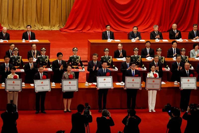 中國今日舉行全國對抗肺炎疫情表彰大會,大會由中國國務院總理李克強主持,中國國家主席習近平向獲得國家勳章和國家榮譽稱號的人士頒授勳章獎章。不過台上的領導高層及接受頒獎的人士均未配戴口罩。(路透)