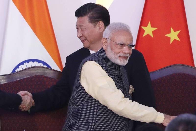 印度學者認為,此時印中關係緊張,印度更應深化與台灣的關係。圖為2016年金磚國家峰會期間,印度總理莫迪(前)與中國國家主席習近平(後)分別與其他領袖握手致意。(美聯社)