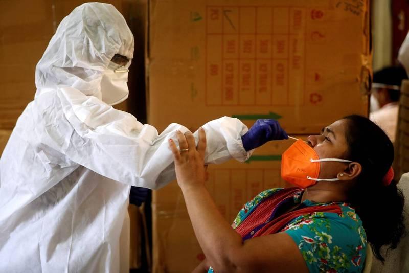 醫護人員7日在印度孟買為民眾進行武肺病毒採檢。(路透)