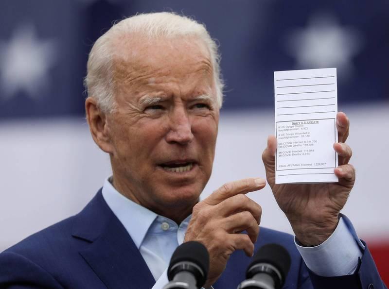 美國民主黨總統候選人拜登(Joe Biden)手握著阿富汗和伊拉克戰爭喪生的士兵人數的紙條。(路透)
