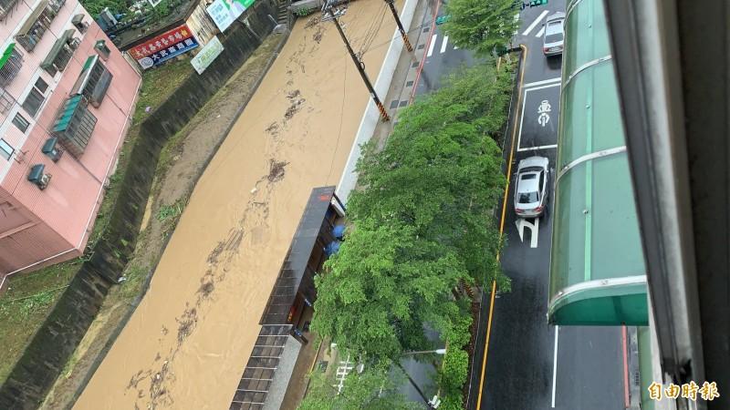 基隆市今天早上豪大雨,瞬間強降雨讓排水系統宣洩不及,圖中左邊為大武崙溪水勢高漲,距離新增建的堤防還剩下一段距離就溢堤,民眾經過基金二路請小心通過。(記者俞肇福攝)