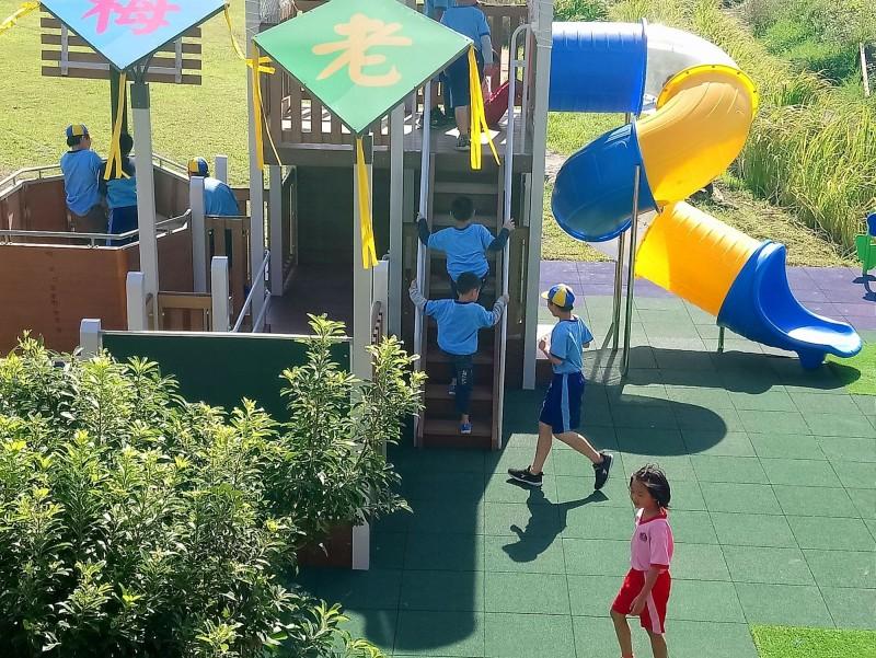 石門區老梅國小從風雨操場延伸出來的彩色溜滑梯,高低落差2層樓高。(圖由新北教育局提供)